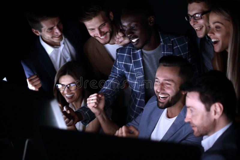Fin vers le haut Les hommes d'affaires gais regardent l'écran d'ordinateur photo stock
