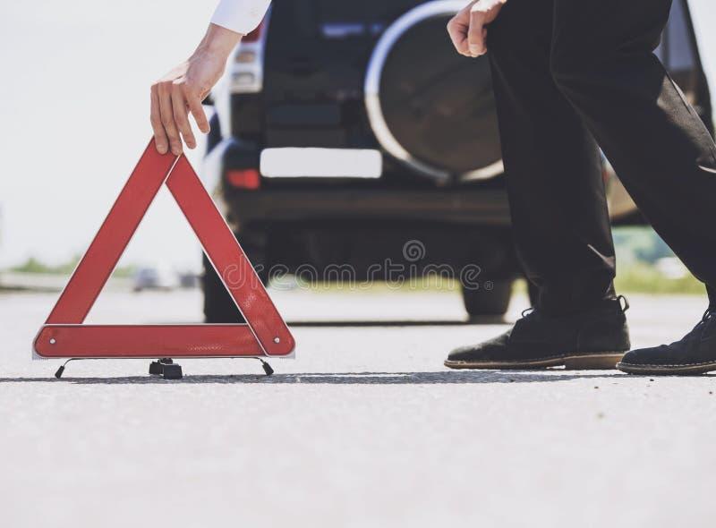 Fin vers le haut Les hommes ont mis la triangle d'avertissement rouge avec la voiture photo stock