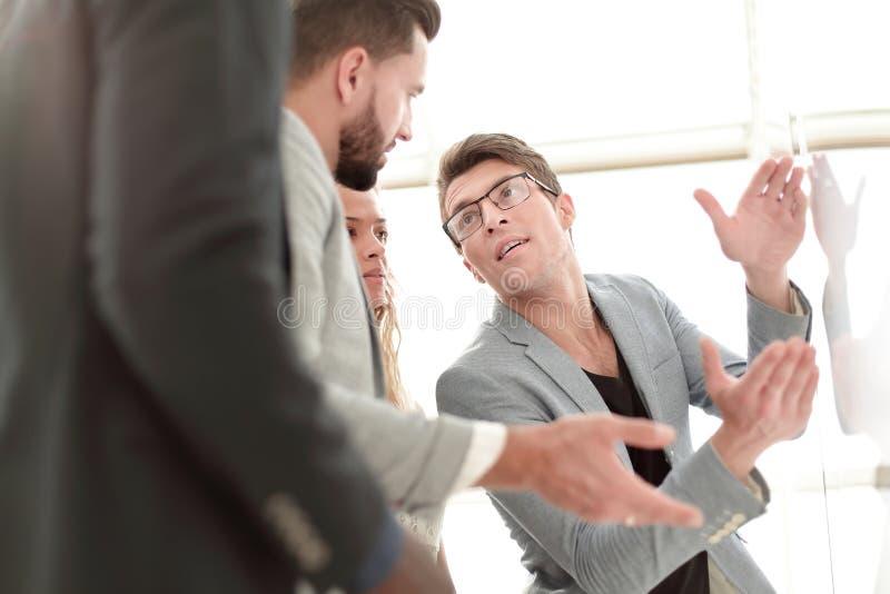 Fin vers le haut parler d'équipe d'affaires, se tenant près du flipchart image stock