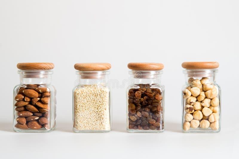 Fin vers le haut Placez des pots en verre de cuisine ? l'int?rieur de contenez les raisins secs, s?same, noisettes, amande Fond b photo libre de droits