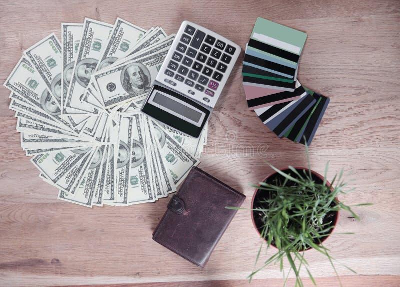Fin vers le haut portefeuille, cartes de crédit et billets d'un dollar présentés sur une table en bois image stock