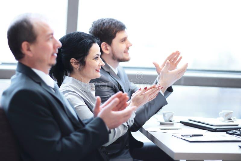 Fin vers le haut ?quipe d'affaires applaudissant l'orateur, s'asseyant dans le lieu de travail images libres de droits