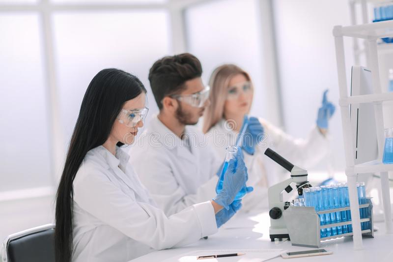 Fin vers le haut scientifique de femme regardant le tube avec le liquide photographie stock