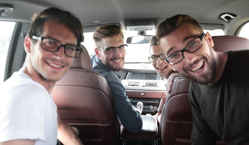 Fin vers le haut un groupe d'amis s'asseyant dans la voiture photos stock