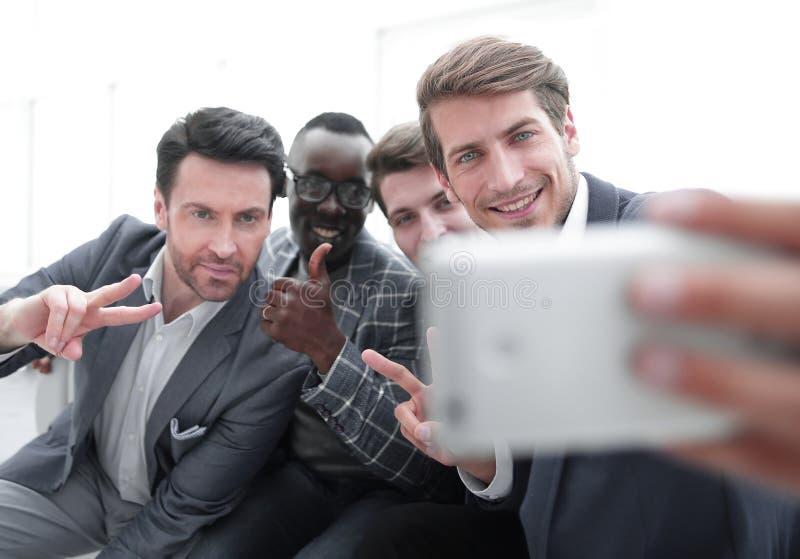 Fin vers le haut un groupe de jeunes employ?s prend un selfie image libre de droits