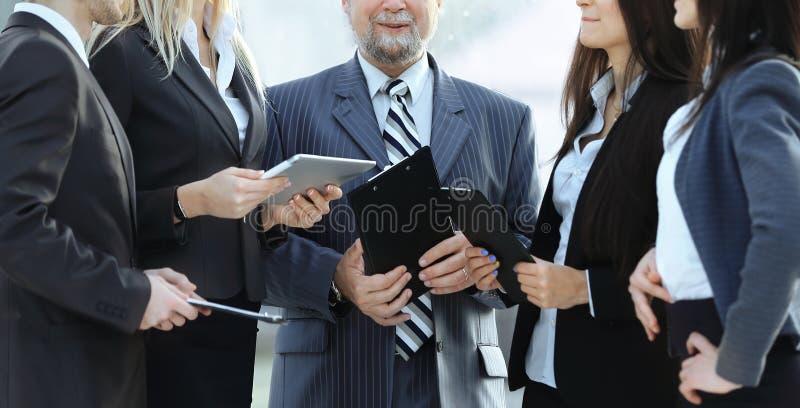 Fin vers le haut une ?quipe d'affaires se tenant parlante dans le bureau photographie stock libre de droits