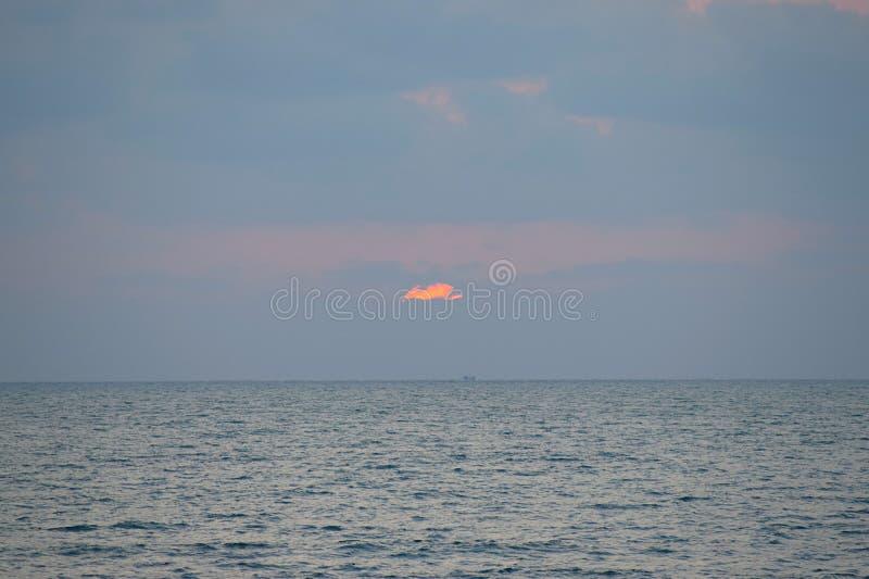 Final del día - puesta del sol sobre el mar con el cielo nublado, playa de Ladghar, Dapoli, la India fotografía de archivo libre de regalías