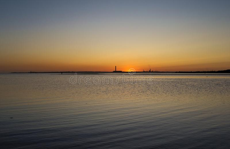 Final glimpse of the setting Sun. Final glimpse of the Sun before it sinks below the horizon on the coast, a tall chimney from a power station is silhouetted royalty free stock photography