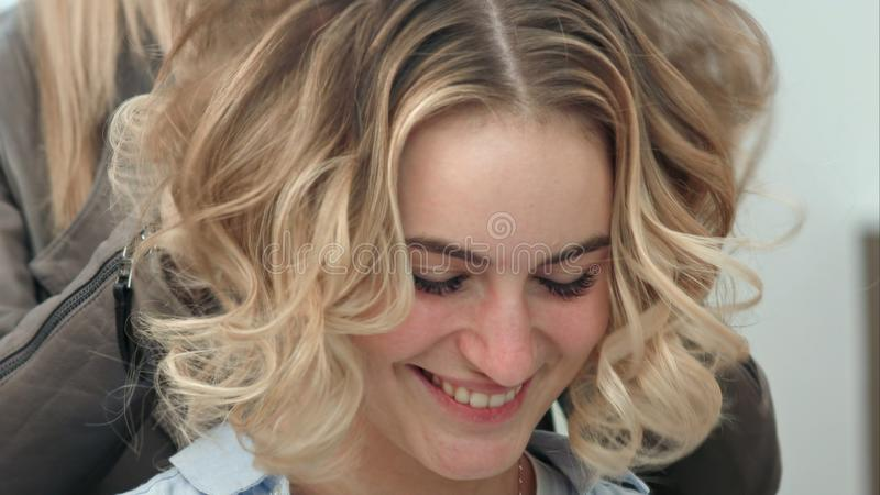 The final styling of curly hair of model by hairdresser in beauty salon royalty free stock photography