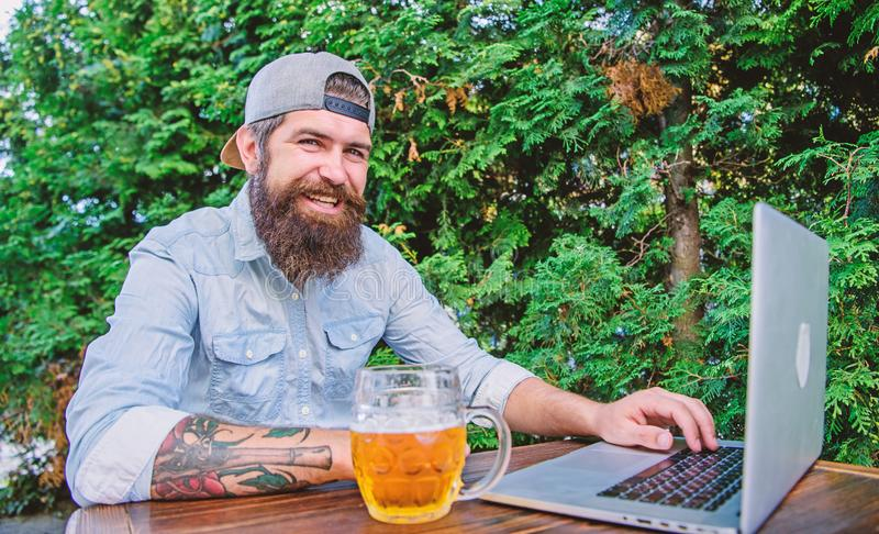 Finally friday. Brutal man leisure with beer and online game. Hipster relax sit terrace outdoors with beer. Bearded. Hipster freelancer enjoy end of working day royalty free stock images