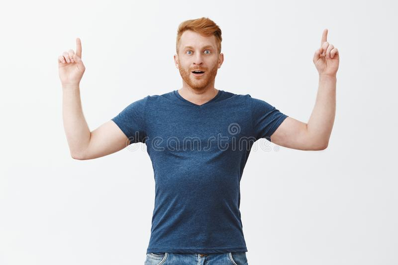 Finally reach top of success, cannot believe. Portrait of impressed excited and amazed handsome adult redhead with. Bristle in blue t-shirt, pointing up with royalty free stock image
