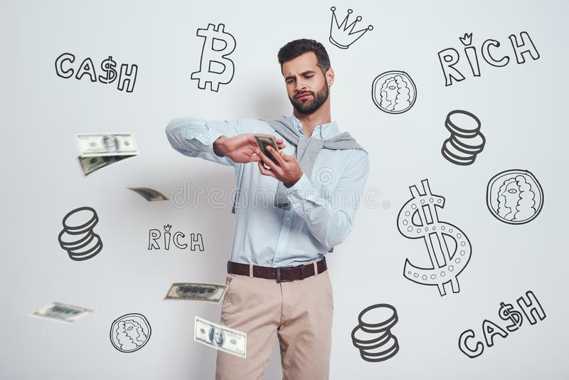 Finally rich. Confident bearded man is scattering dollars while standing against grey background with different doodle. Illustrations on it. Wealth concept stock photography