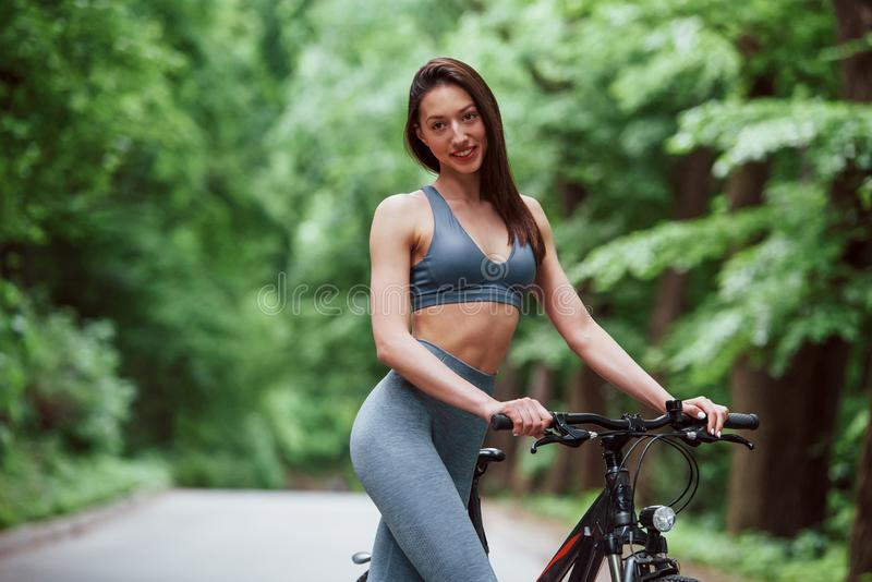 Finally it`s summer. Female cyclist standing with bike on asphalt road in the forest at daytime stock photos