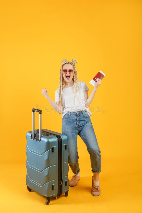 Finally a vacation. Woman traveler with suitcase, passport and flight ticket on yellow background.  stock image