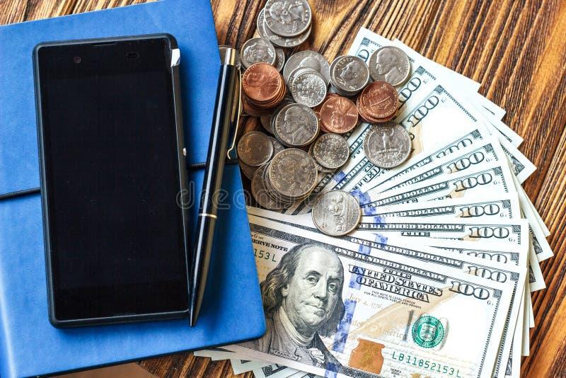 A finança do negócio e salvar o conceito do dinheiro Close up das notas de dólar, das moedas, do telefone, da pena e do caderno d fotos de stock