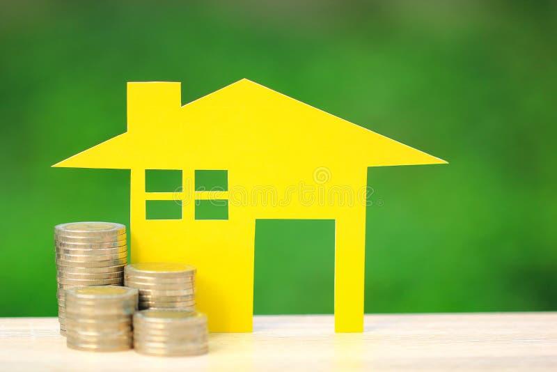 Finança, modelo amarelo da casa e aderência do dinheiro das moedas no fundo, no negócio do investimento e no conceito verdes natu imagens de stock