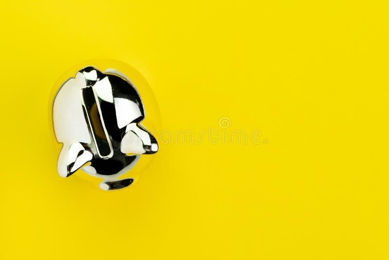 Finança, operação bancária, economias ou conceito do investimento, mealheiro de prata brilhante no fundo amarelo contínuo com esp fotografia de stock