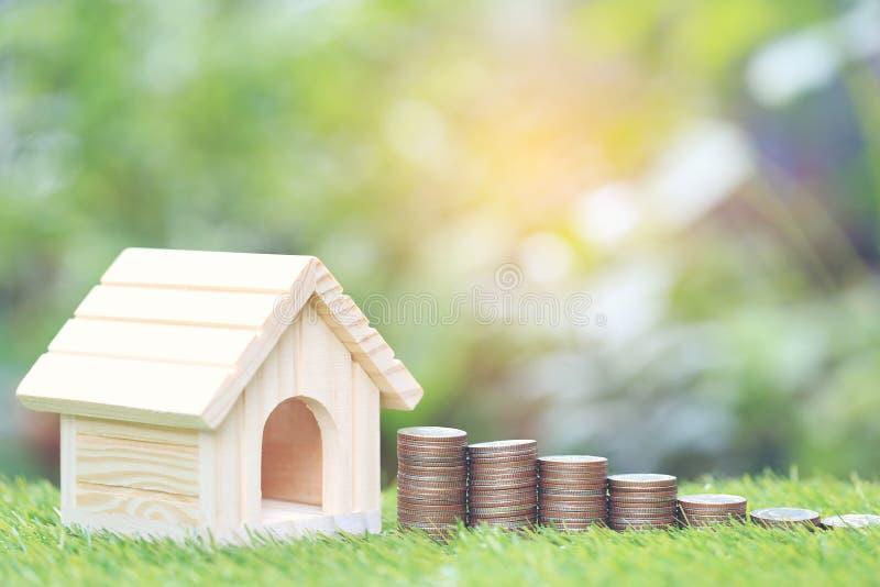 Finança, pilha de dinheiro das moedas e casa modelo no backgroundd verde natural, salvar para para preparar-se no futuro fotos de stock royalty free