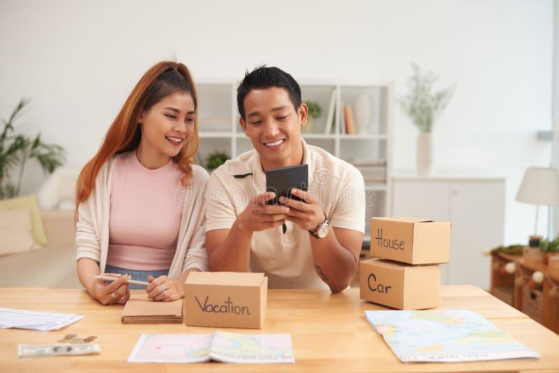 Finanças asiáticas de sorriso do planeamento dos pares foto de stock royalty free