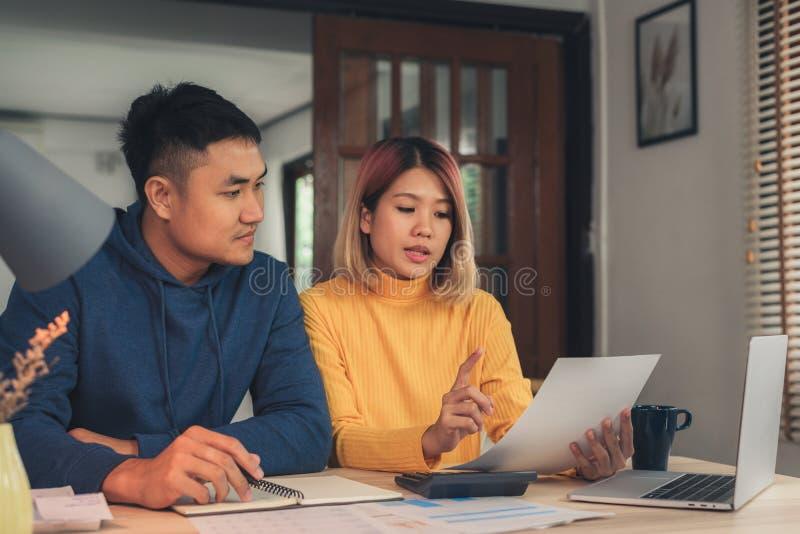 Finanças de controlo dos pares asiáticos novos, revendo suas contas bancárias usando o laptop e a calculadora na casa moderna imagens de stock royalty free