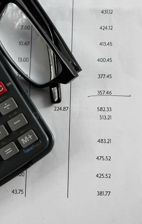 Finance bank statement. Bank statement with glasses and calculator royalty free stock image