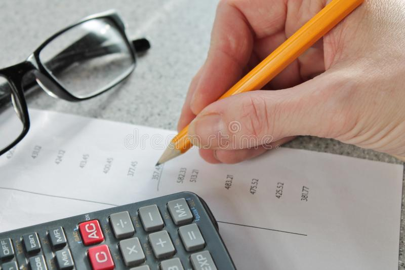 Finance bank statement numbers maths calculator. Bank statement with pencil, glasses and calculator numbers in columns stock photography
