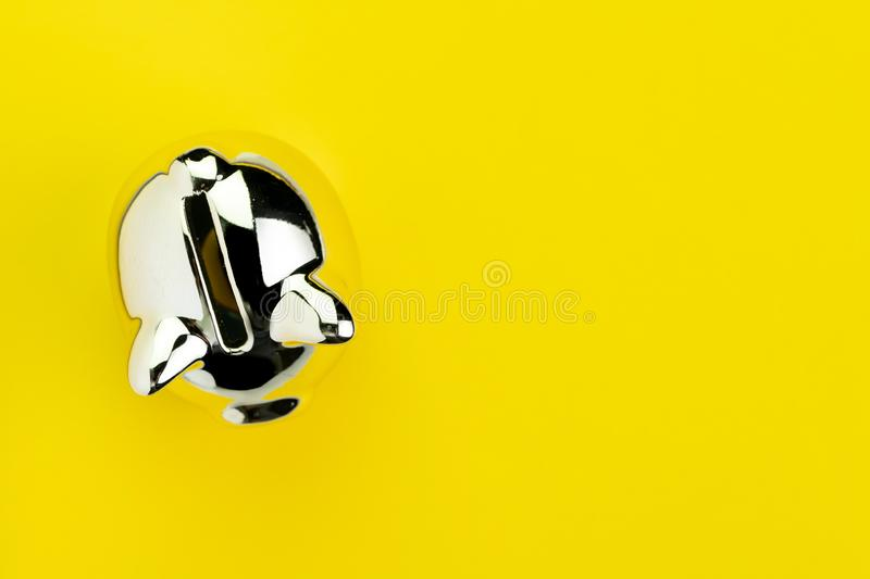 Finance, banking, savings or investment concept, shiny silver piggy bank on solid yellow background with copy space.  stock photography