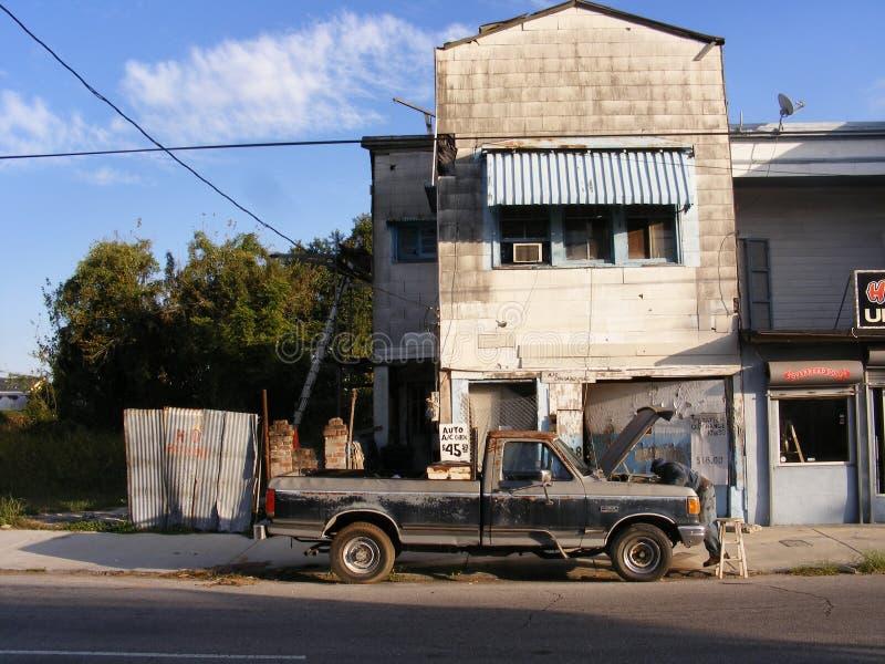 Finance-bas homme de région de ville de revenu fixant le vieux camion image stock