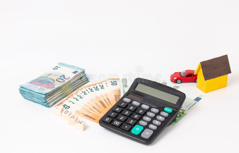 Finance and car loan, saving money for a car. Red car and euro banknotes. Calculator, euro money and House. Wooden cubes with word royalty free stock photos