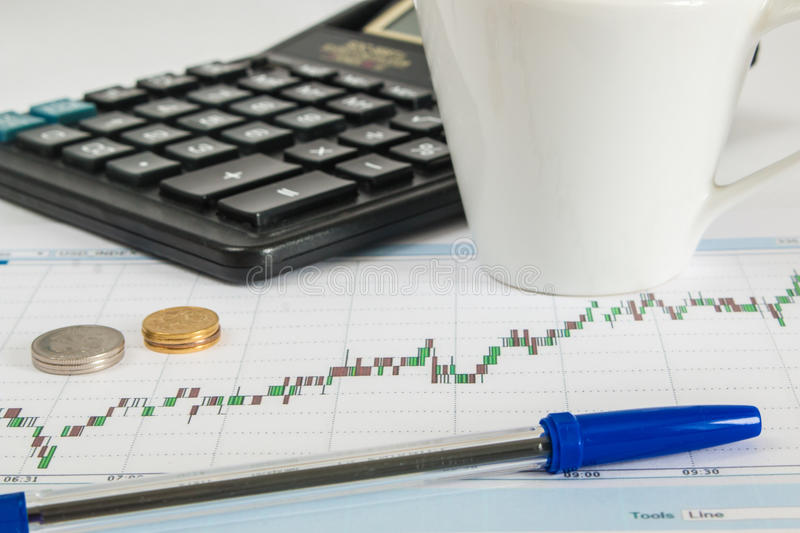 Finance graph on a white background with calculator, cup of coffee an office desk at morning royalty free stock photo