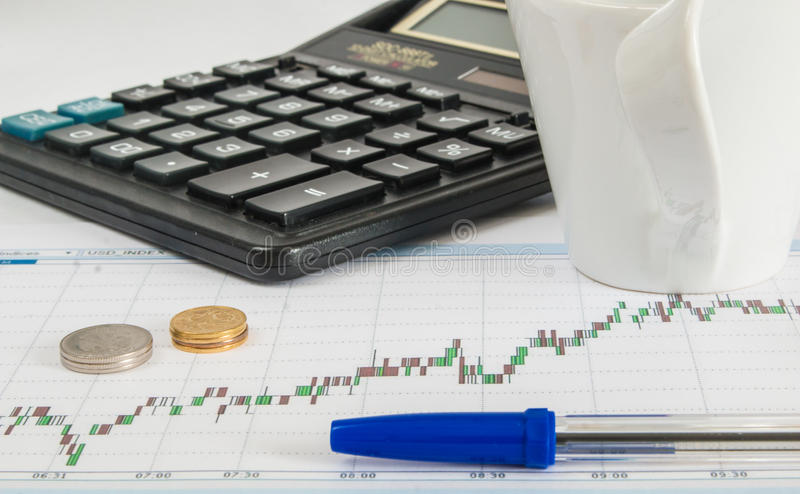 Finance graph on a white background with calculator, cup of coffee an office desk at morning stock images