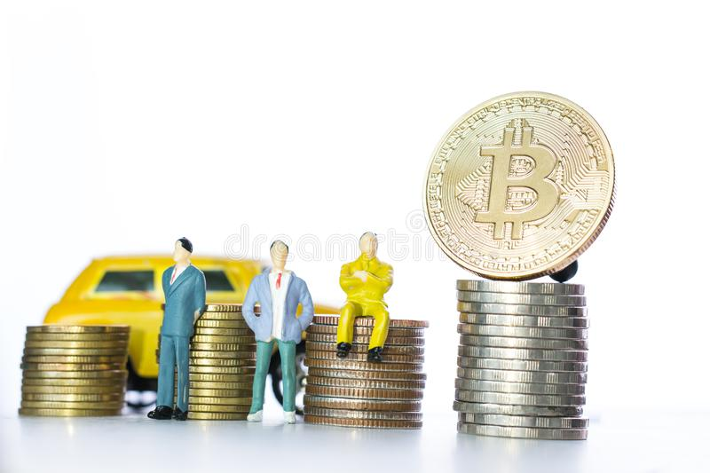 Finance investment risk Internet concept: Miniature business standing near Bitcoin Digital Virtual money on stack coins. stock images