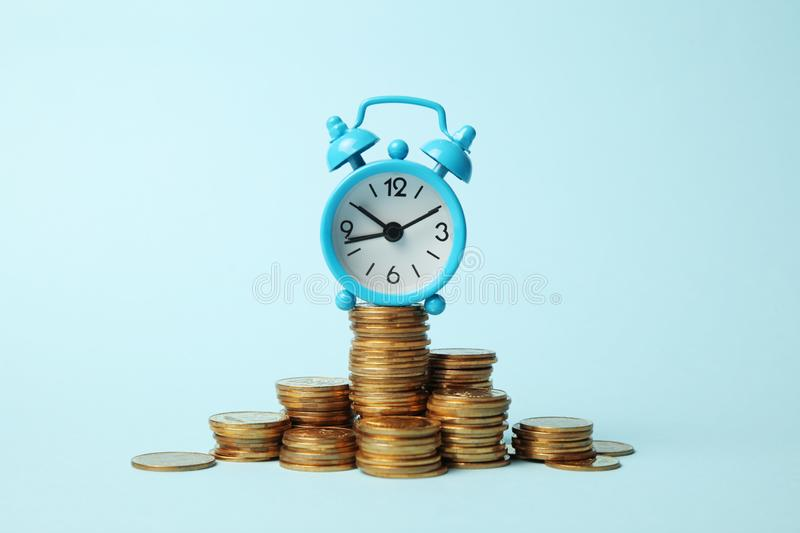 Finance investment, Time is money. Alarm clock and golden money coins, pension stock photography