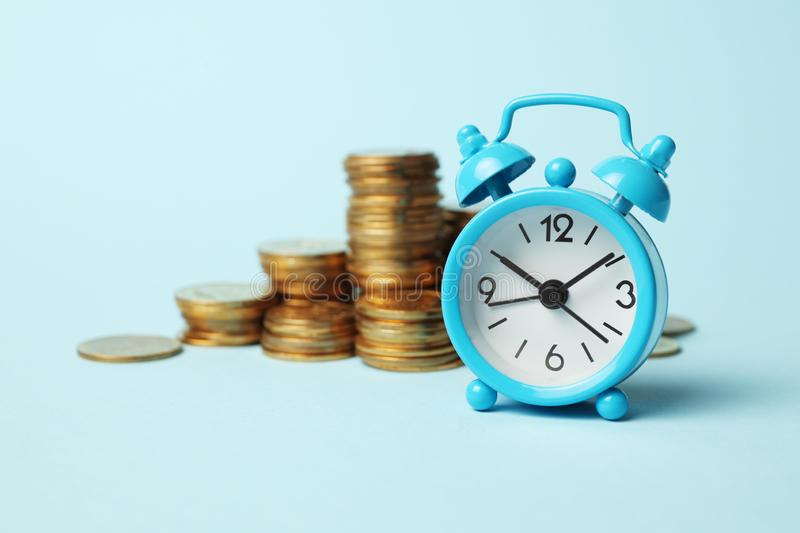 Finance investment, Time is money. Alarm clock and golden money coins, pension royalty free stock photos
