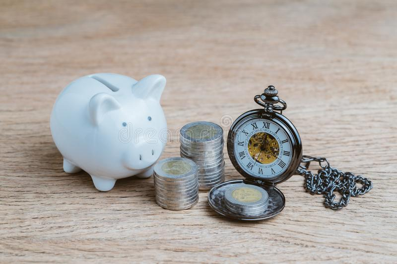 Finance or long term saving money and investment concept, white piggy bank and coins stacked and pocket watch on wood table.  royalty free stock photos