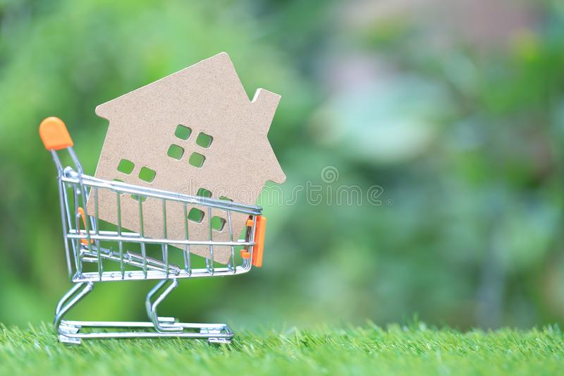 Finance, Model house in mini shopping cart on natural green background, Business investment and real estate.  stock photos