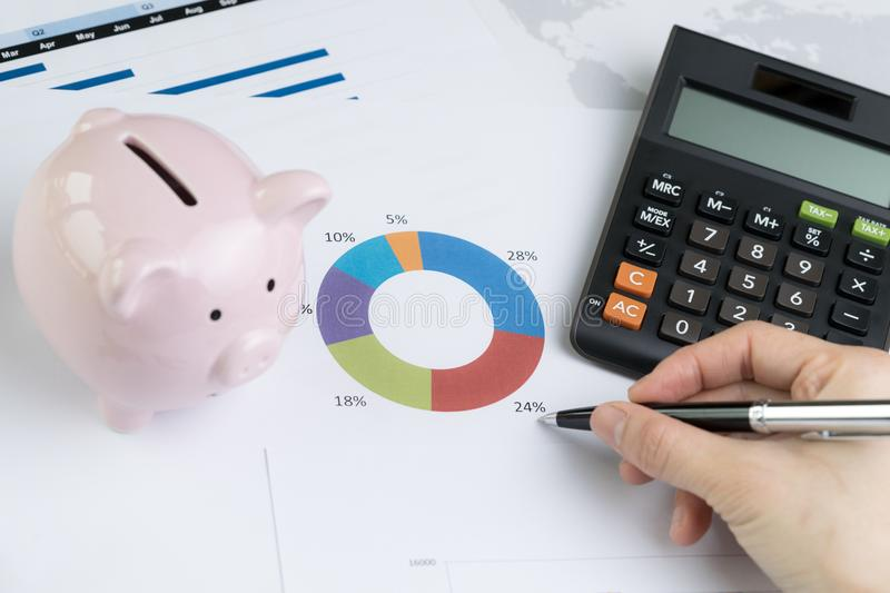 Finance, money budget planning or investment asset allocation co. Ncept, hand holding pen reviewing pie chart and graph with calculator and pink piggy bank on royalty free stock photo