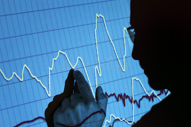 Finance presentation. Silhouette of a businessman pointing to a projected graph at a presentation stock image