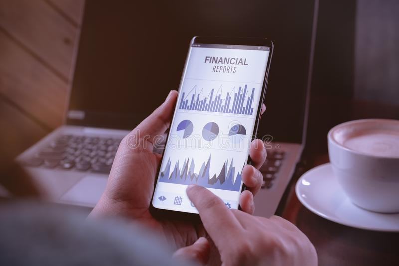 Finance reports data analytics concept. Close up of young business woman holding smart phone with financial reports mobile stock images