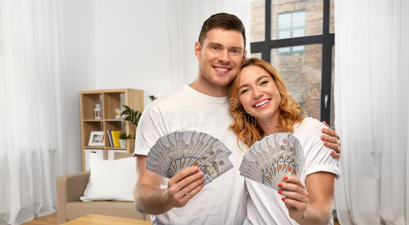 Happy couple in white t-shirts with dollar money royalty free stock photo
