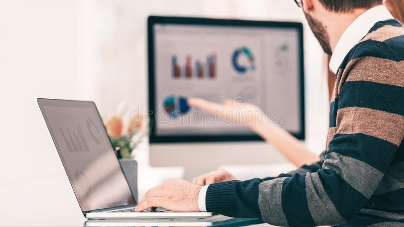 Finance specialist working on laptop with financial charts and marketing schemes royalty free stock photos