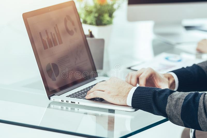 Finance specialist working on laptop with financial charts and stock photography