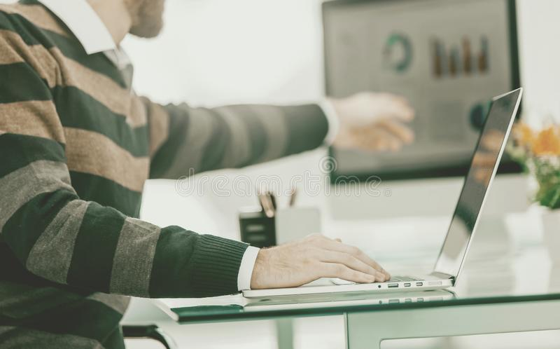 Finance specialist working on laptop with financial charts and royalty free stock photo