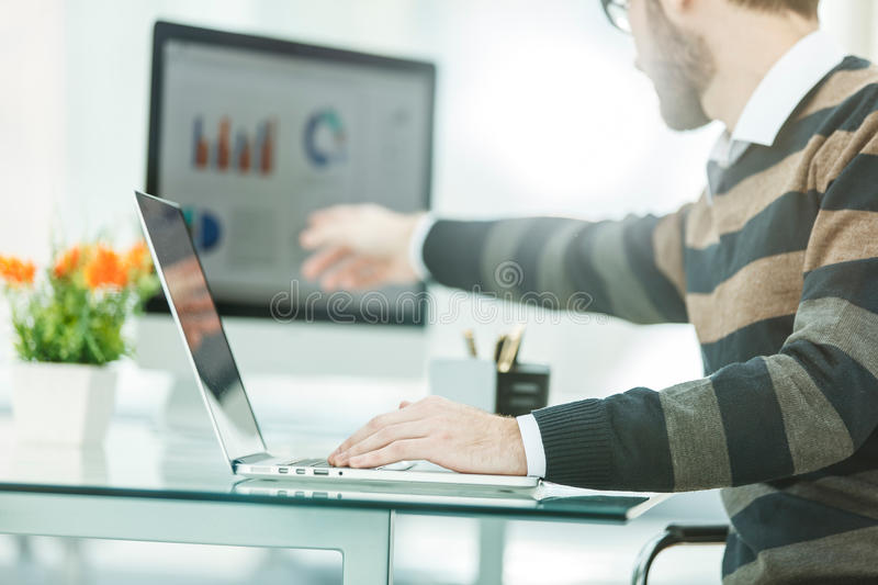 Finance specialist working on laptop with financial charts and marketing schemes royalty free stock image