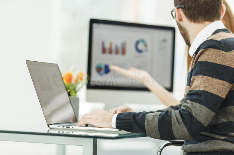 Finance specialist working on laptop with financial charts and marketing schemes royalty free stock photo