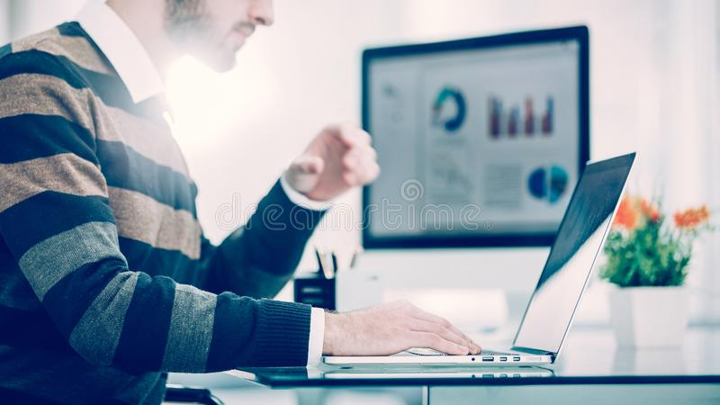 Finance specialist working on laptop with financial charts and marketing schemes royalty free stock images