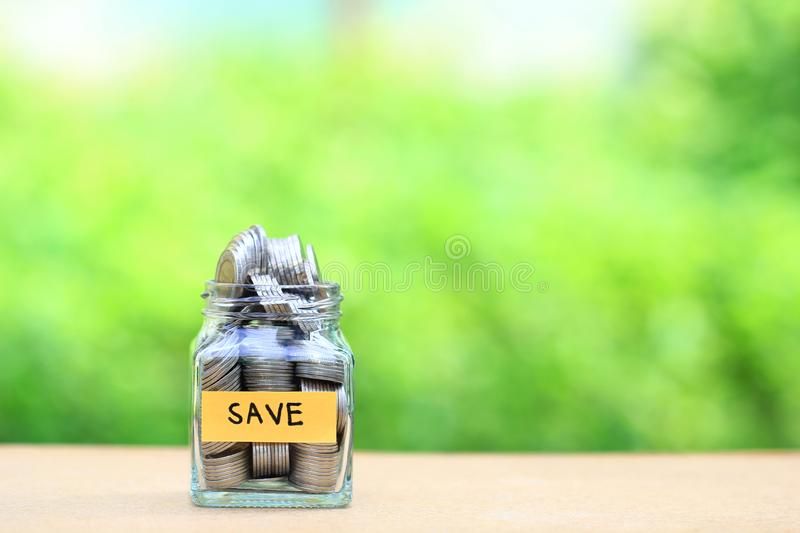 Finance, Stack of coins money in the glass bottle on natural green background, Save money for prepare in future and retirement. Concept royalty free stock image