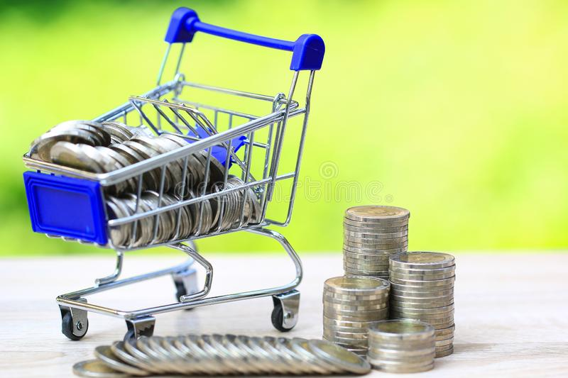 Finance, Stack of coins money in mini shopping cart on natural green background, Business investment growth and Save money for. Prepare in future concept stock image