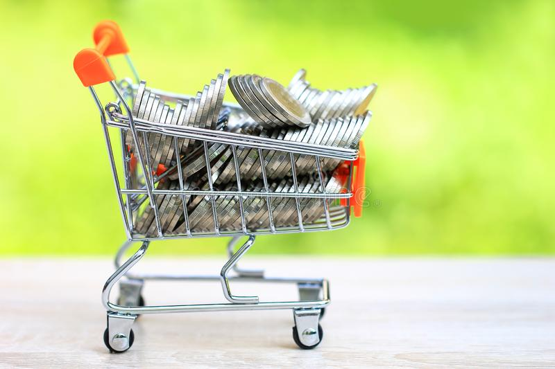 Finance, Stack of coins money in mini shopping cart on natural green background, Business investment growth and Save money for. Prepare in future concept stock photo