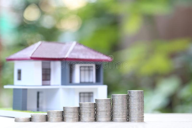 Finance, Stack of coins money and Model house on natural green background, Business investment and real estate.  royalty free stock images